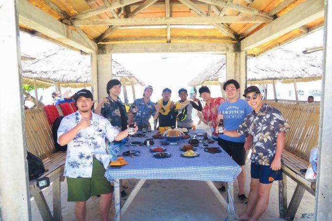韓流ホッピングでランチを小屋の中で食べる男性5人とスタッフ