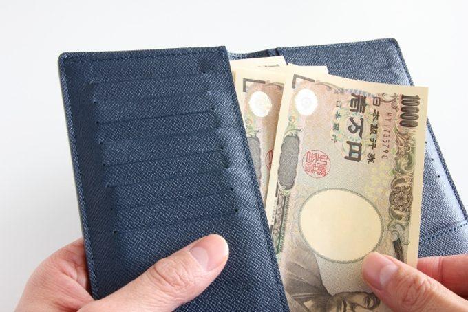 お金を財布にいれているイメージができる写真