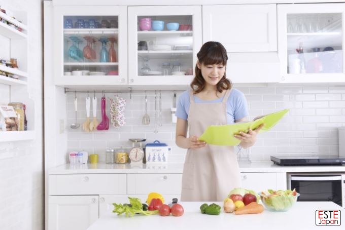 レシピを見ながら料理する女性