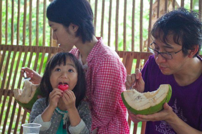 カカオ農園ツアーで果物を食べている家族の写真