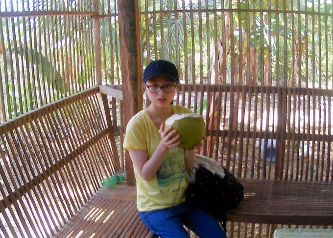 カカオ農園でココナッツを飲む女性