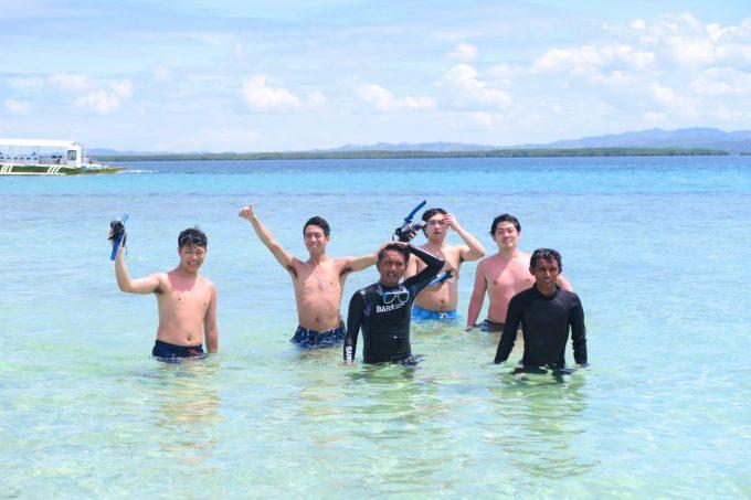 韓流ホッピングのスタッフと海で写真を撮る男性4名