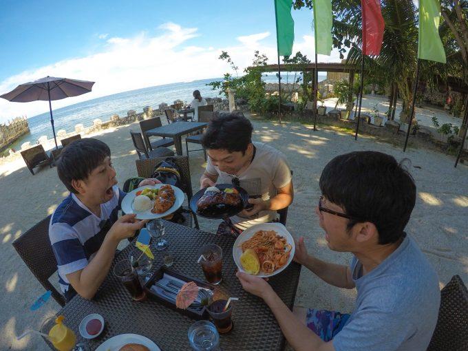 ダイナミックツアーで昼食を食べる男性3人の写真