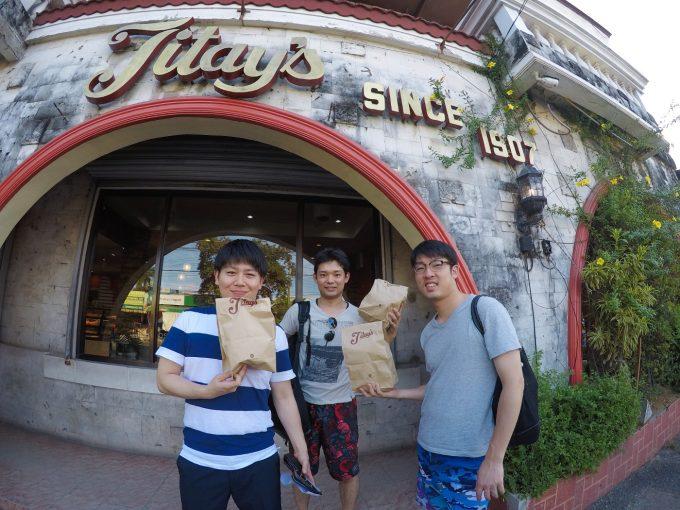 パン屋さんでお土産を購入する男性3人の写真