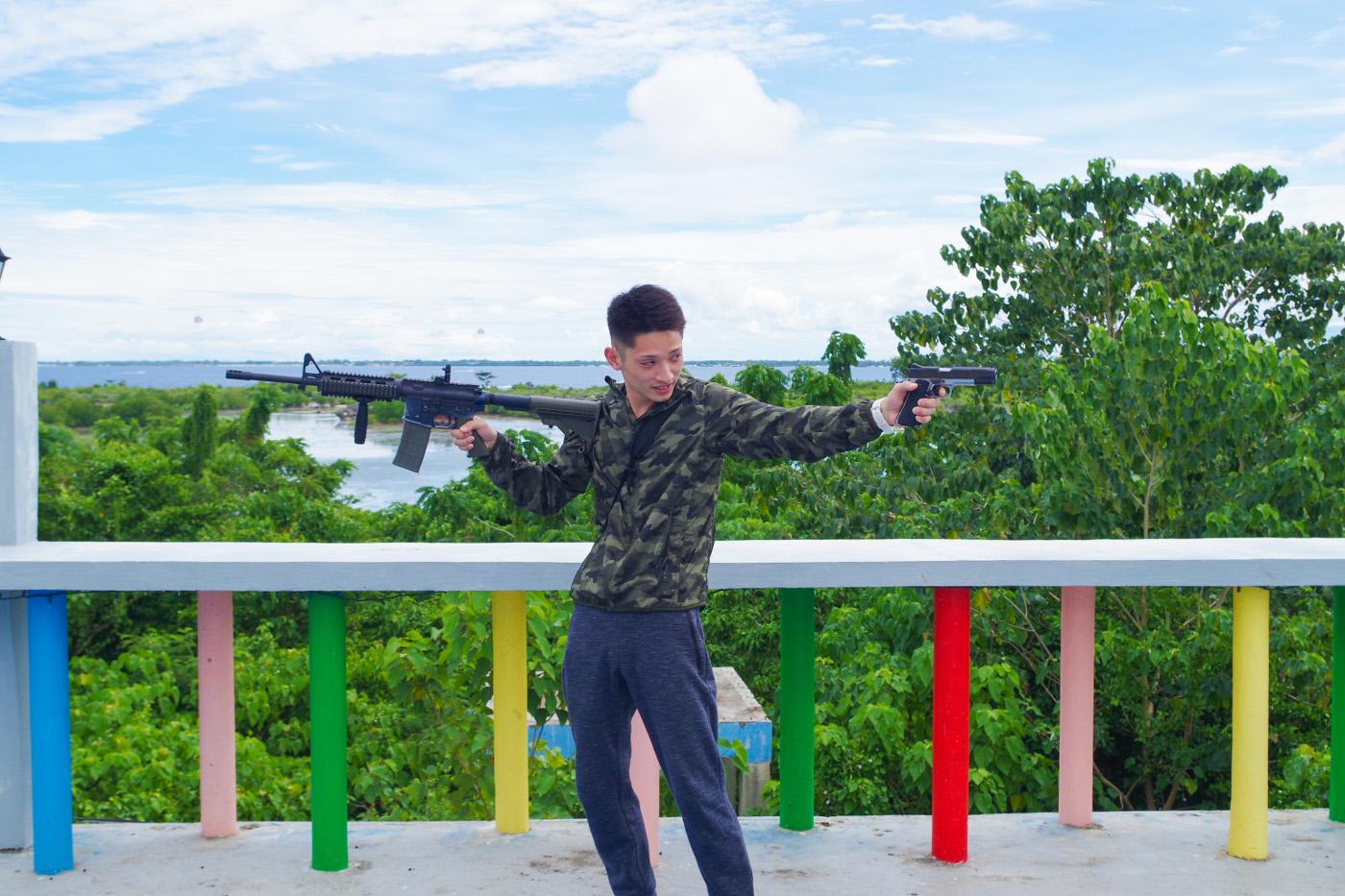 ライフルとハンドガンを構える男性