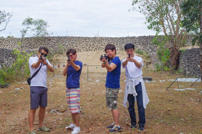 実弾射撃場で銃を向ける男性4人