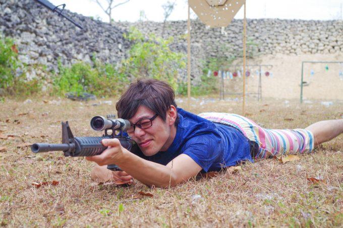 実弾射撃場で寝そべってスナイパーライフルを構える男性