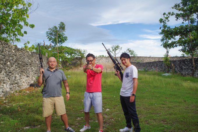 射撃場で拳銃とライフルを構える男性3人