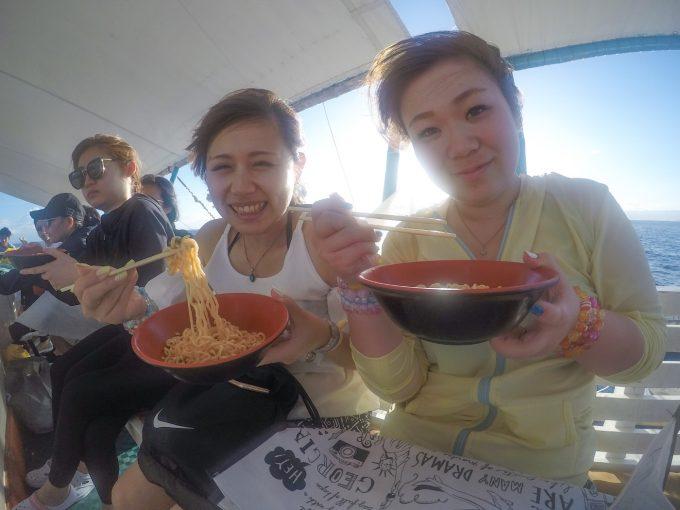 辛ラーメンを船で食べる二人の女性の写真