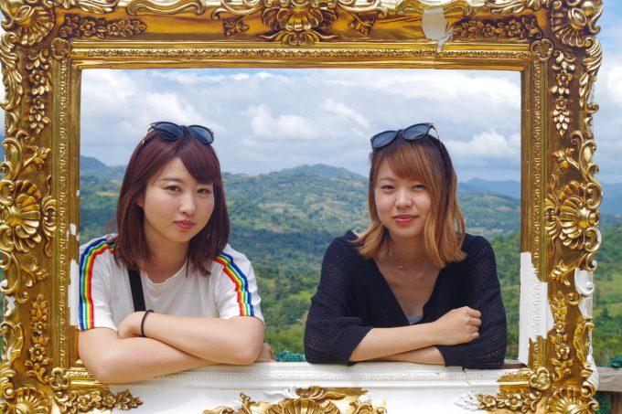 額のモチーフに手をつく女性2人