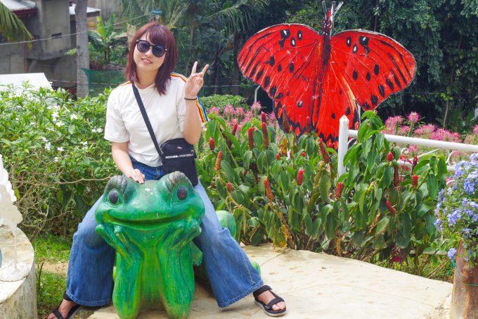 カエルの置物に乗る女性