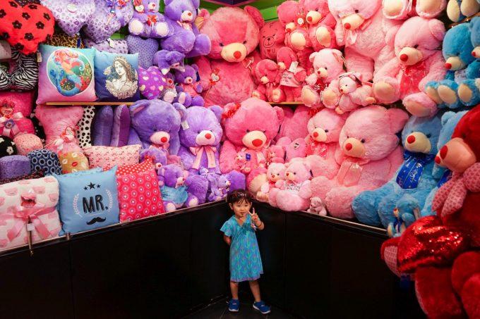 ピンクのぬいぐるみに囲まれた女の子の写真