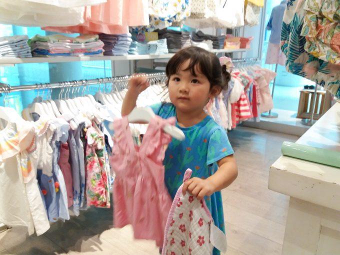 洋服を選んでいる少女の写真