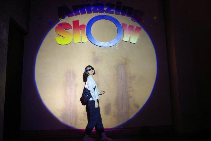 サングラスをかけてアメージングショーの舞台に立つ女性