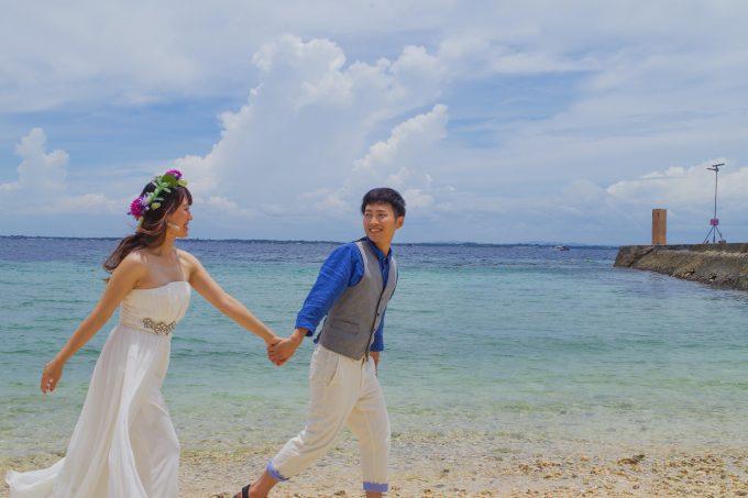 ビーチで新郎と新婦が歩いてる写真