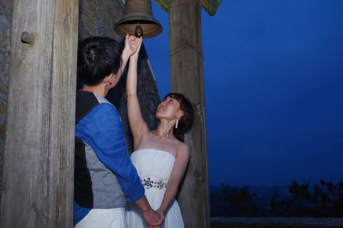 トップスで鐘を鳴らす新郎新婦の写真