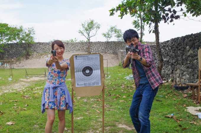 射撃場で銃を構えるカップル