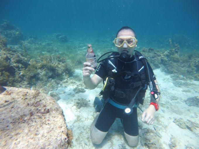 海底でビール瓶を持ってる男性