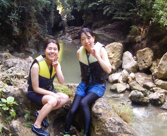滝を背景にしている女性2人