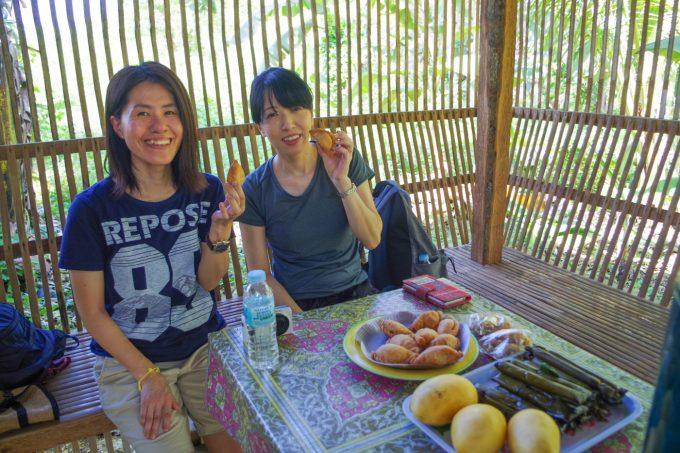カカオ農園で昼食を食べている女性2人