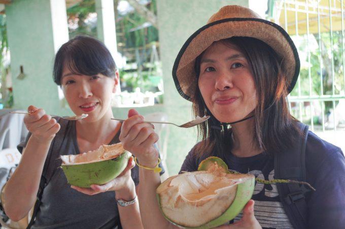 フレッシュココナッツを食べている女性2人