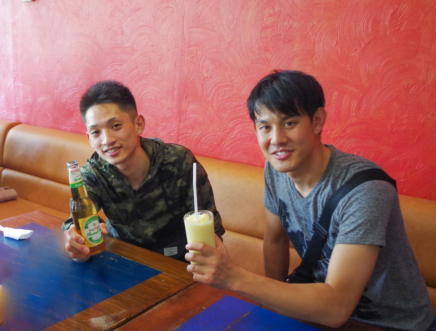 ビールを持つ男性とマンゴーシェイクを持つ男性