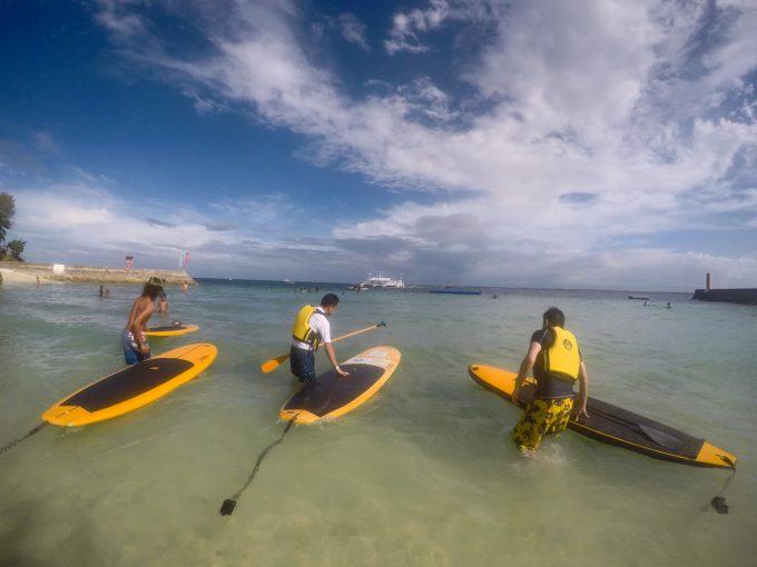 SUPを海に浮かべ出発する男性3人
