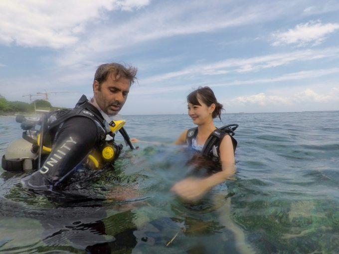 海で体験ダイビングを始める女性とインストラクター