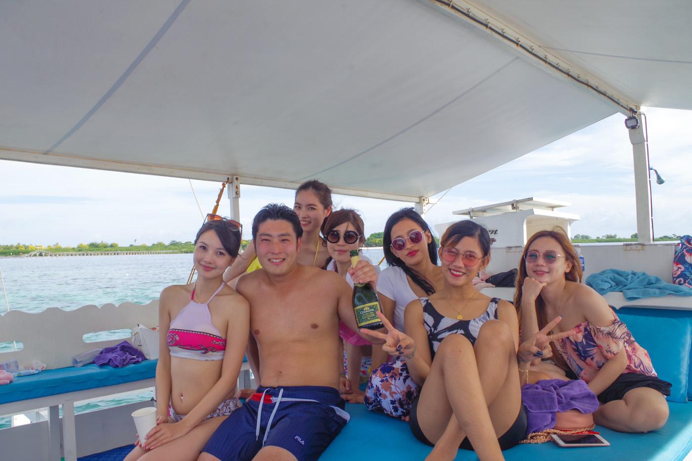 水着美女6人に囲まれてシャンパンを持っている男性