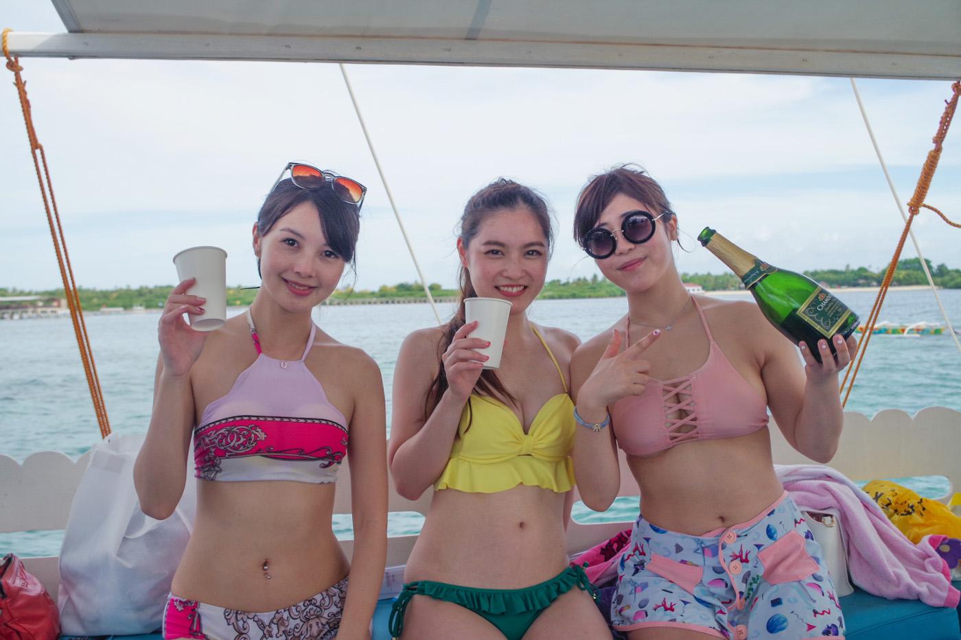 シャンパンを船上で飲む女性3人