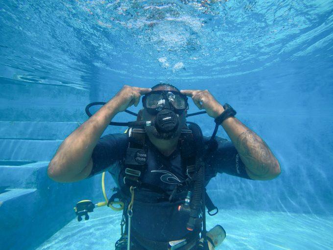 水中でゴーグル内の水を抜く男性