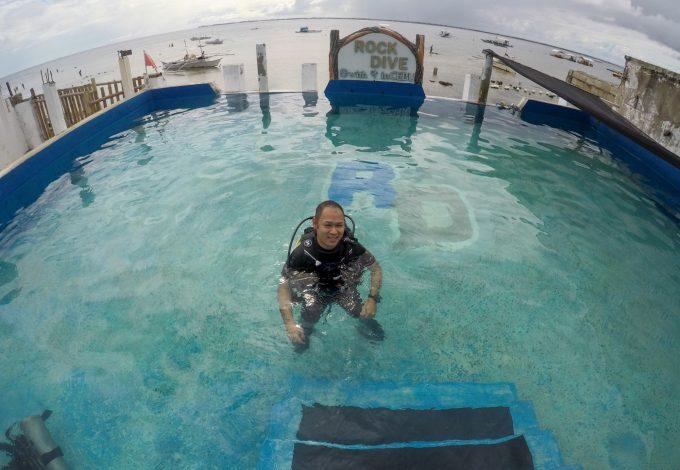 ダイビング練習用のプールで浮いている男性