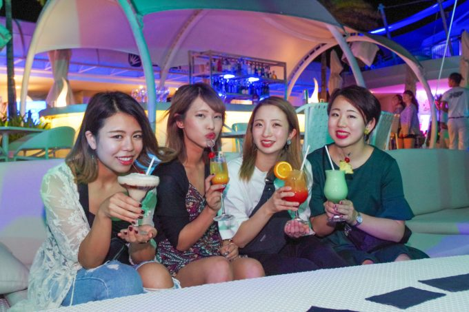 カラフルなカクテルを飲む女性4人