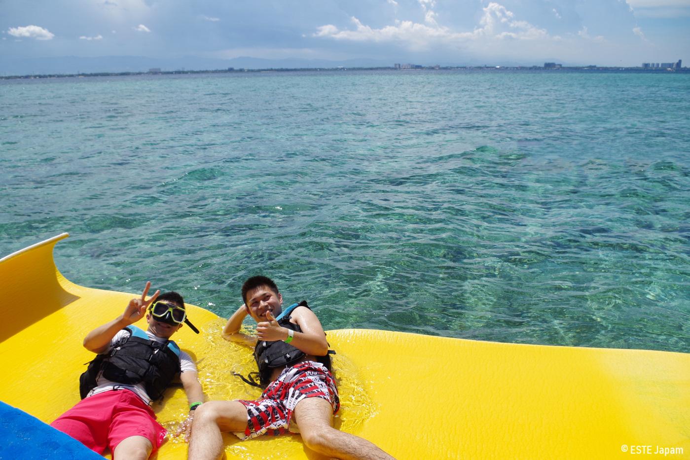 貸切ボートのウォーターマットに寝そべる男性2名