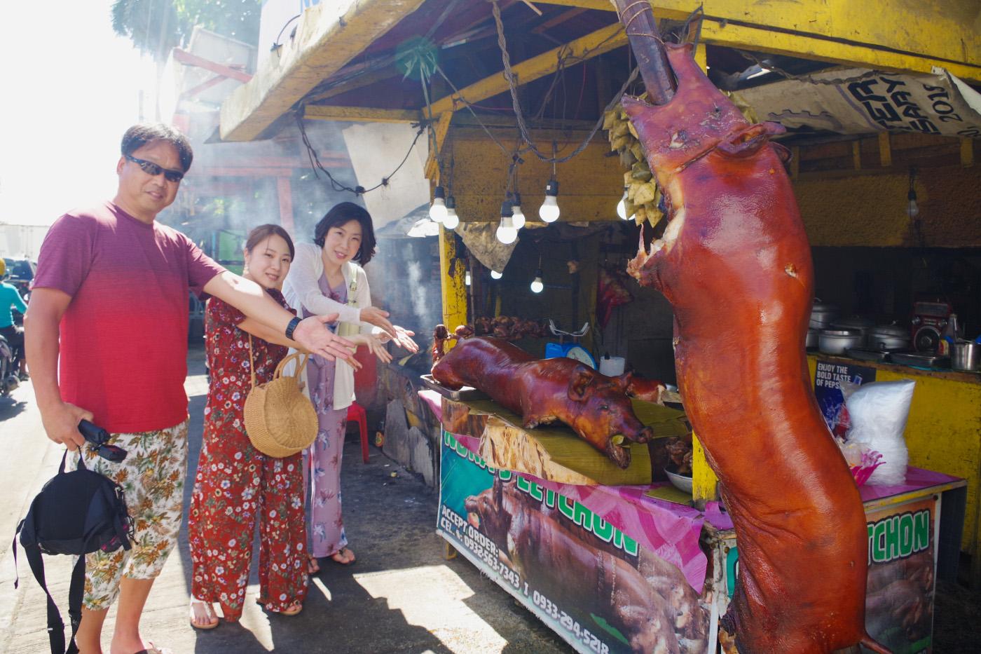 レチョン売場で豚の丸焼きを指さす男性と女性2名