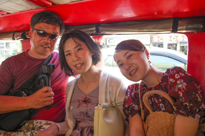 ジプニーの中で写真を撮る男性と女性2名