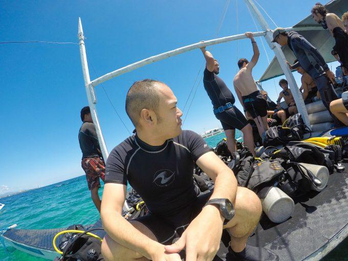 スキューバダイビングでボートの上に座る男性
