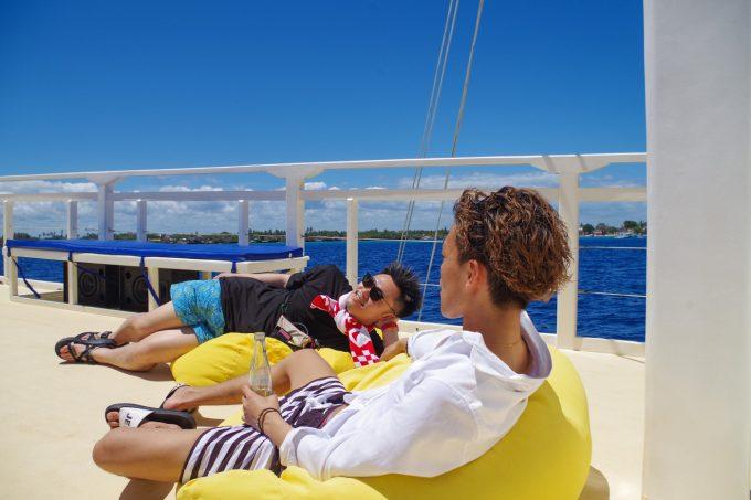 ラグジュアリーボートの2階で寝そべる男性2名