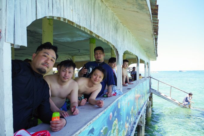 水上レストランで写真を撮る男性4名