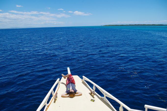 ラグジュアリーボートの船首で寝る男性