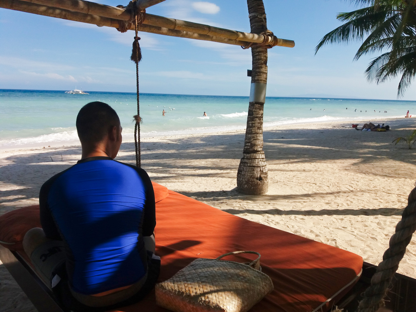 サウスパームホテルのビーチにあるベッドに座る男性