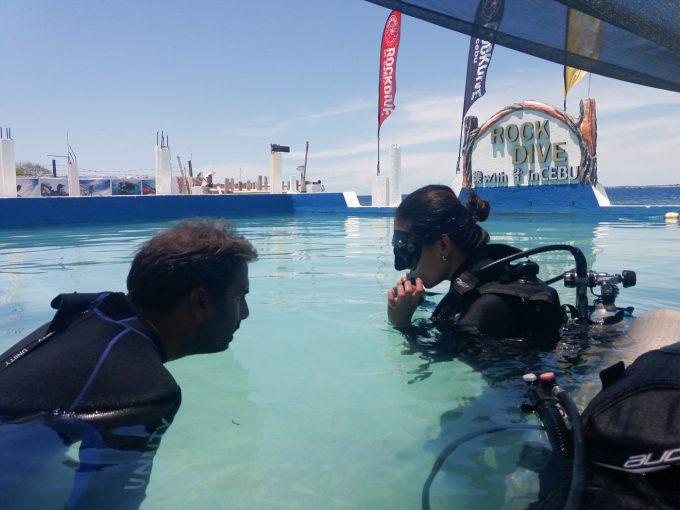 練習用プールでダイビング初心者に教えるインストラクター