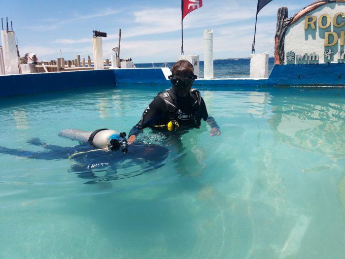 練習用プールでダイビング初心者をサポートするインストラクター