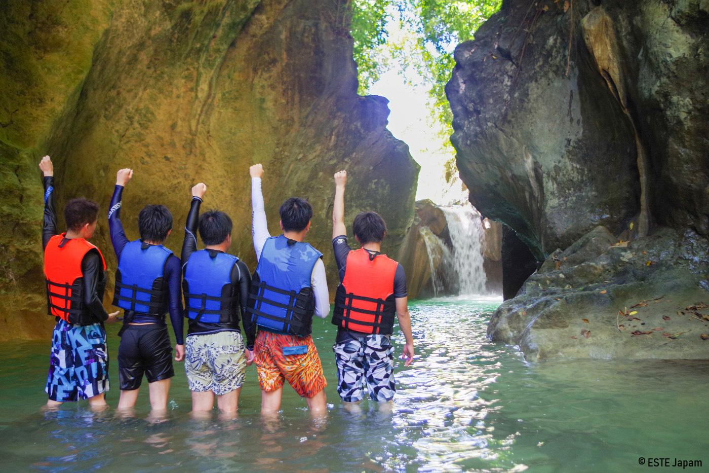 滝に向かって拳を突き上げる男性5名