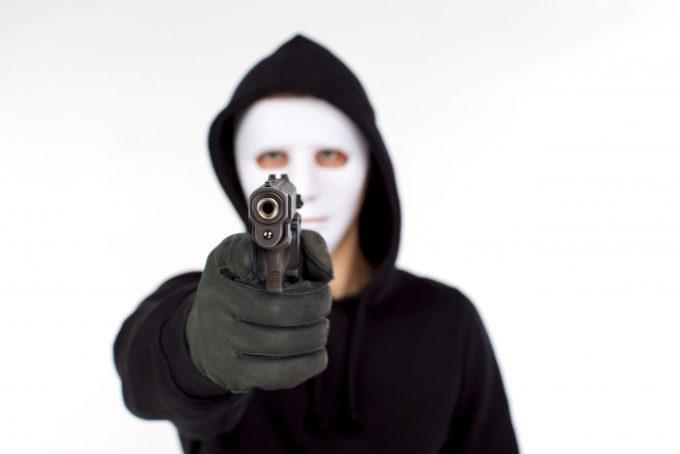 強盗が銃を突きつけるイメージ画像