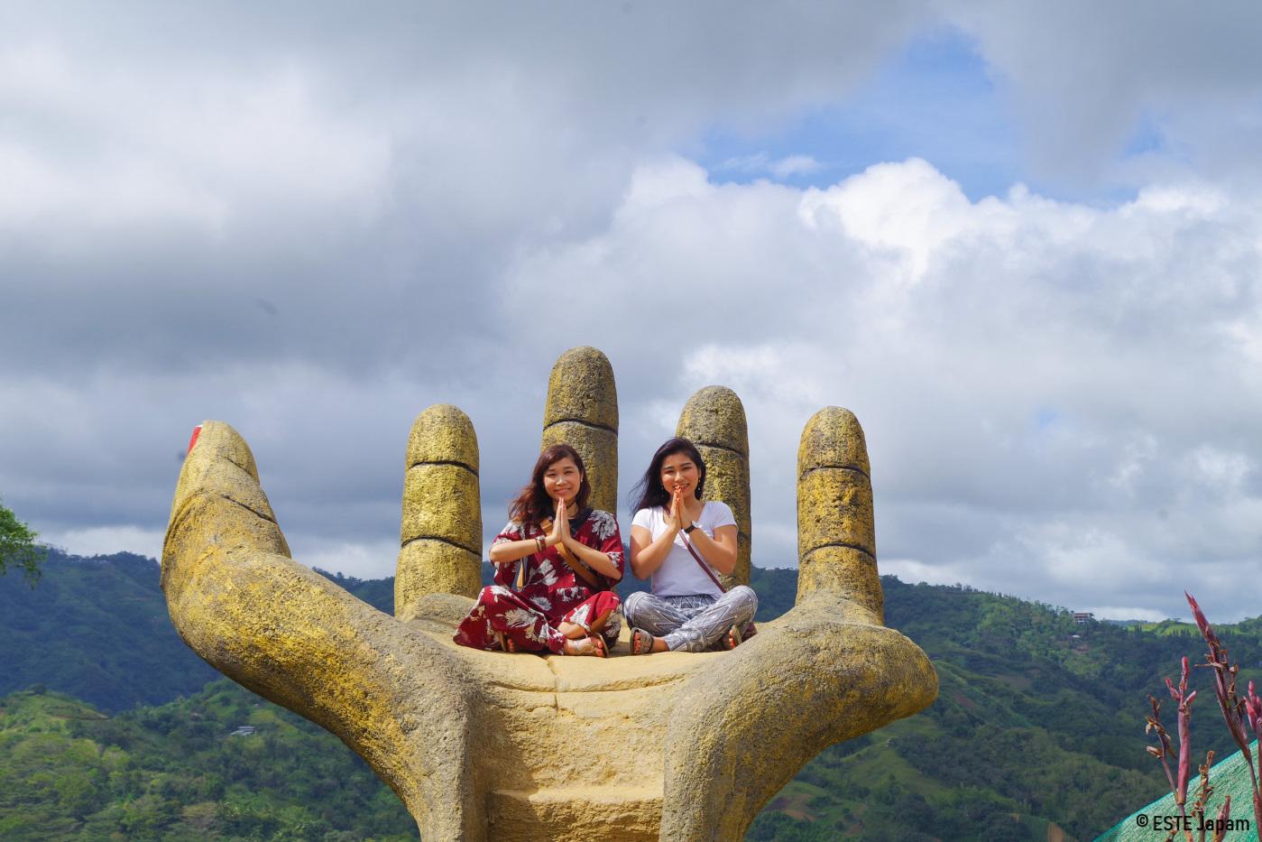 シラオPGCSの手のひらのモニュメントに座る女性2名