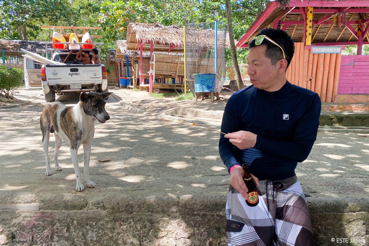 マクタンニュータウンビーチでBBQを犬に分ける男性