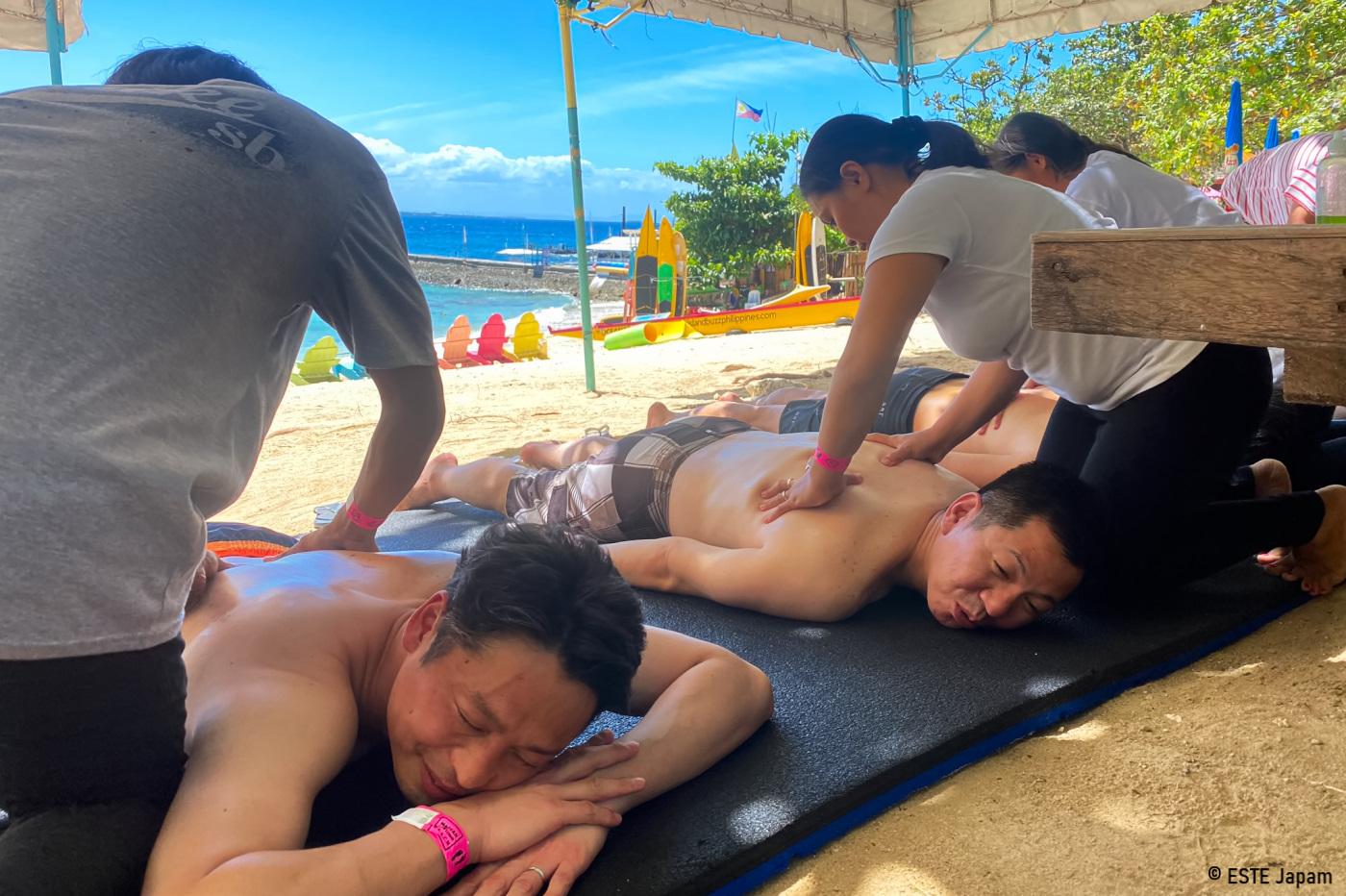 マクタンニュータウンビーチでマッサージを受ける男性2名